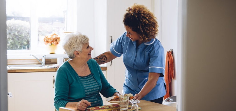 caregiver and a senior woman smiling at each other