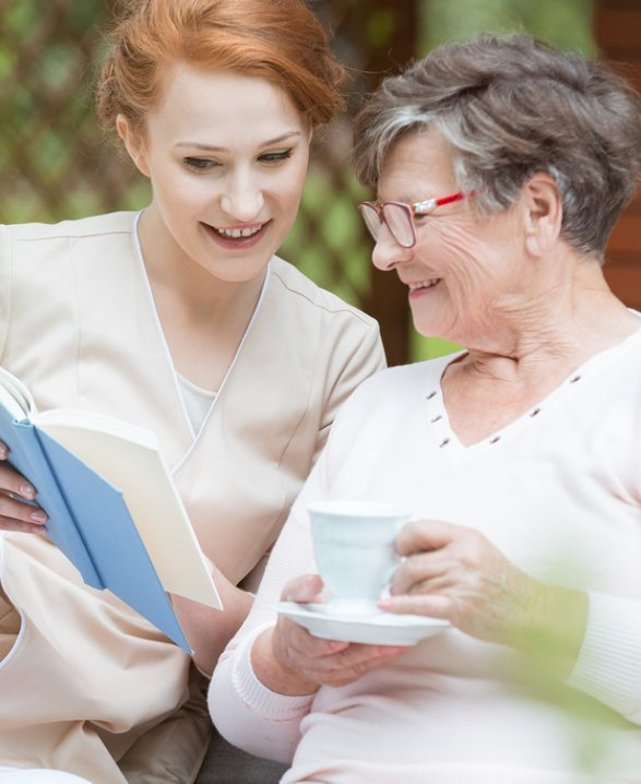 a caregiver and a senior woman laughing