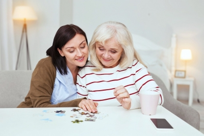 caregiver and senior woman playing with puzzle