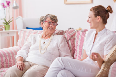 caregiver and senior woman smiling while talking