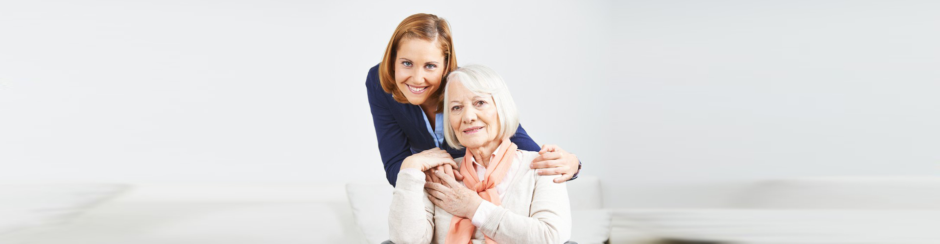 an old lady and a caregiver smiling